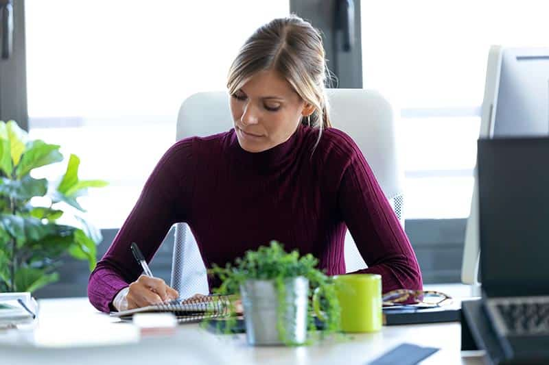 Woman writing notes during zoom meeting at desk