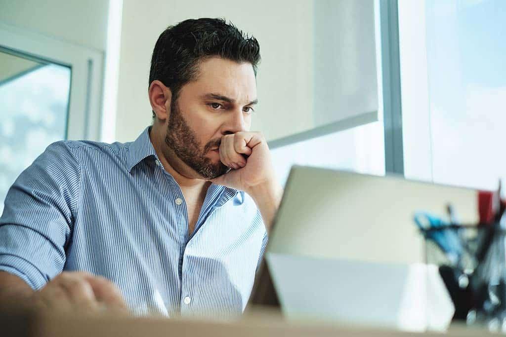 man focused working on laptop